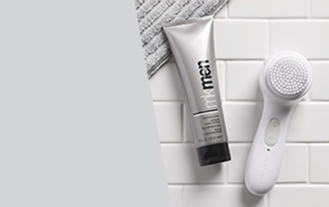 Mary Kay Skinvigorate Sonic Skin Care System shown on white subway bathroom tile with grey towel and MKMen Daily Face Wash