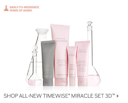 Four Mary Kay products from the new TimeWise Miracle Set 3D skin care regimen are shown in pink and grey packaging in front of glass beakers filled with pink liquid. The set includes the 4-in-1 Cleanser, the Day Cream SPF 30, the Night Cream and the Eye Cream.