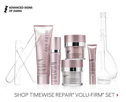 The TimeWise Repair Volu-Firm skin care set from Mary Kay is shown in front of clear glass beakers, including the Eye Renewal Cream, the Lifting Serum, the Foaming Cleanser, the Day Cream with SPF 30 and the Night Treatment with Retinol.